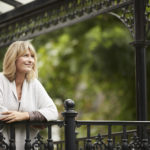 Shot of a mature woman leaning against the railing of her front porch
