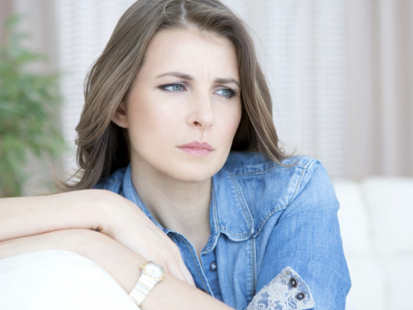 Upset mid-age woman sitting indoors..See more LIFESTYLE images with this MID-AGE WOMAN. Click on any image below for lightbox.