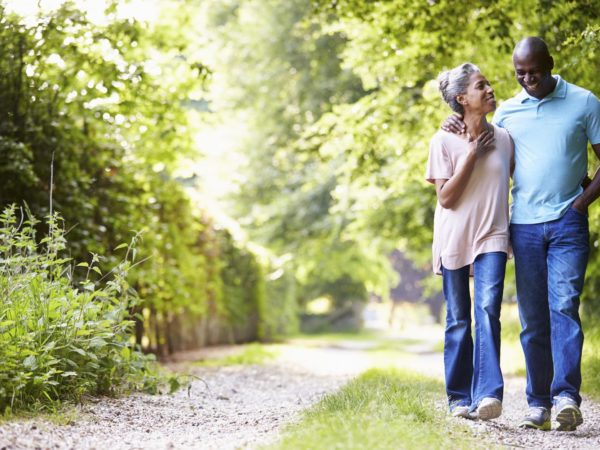 Mature African American Couple Walking In Countryside On Sunny Day