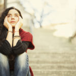 Sad young woman sitting on stairs. There are tears in her eyes