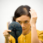 Lifestyle portrait of pretty asian young woman dressing with antique mirror and comb on hands, ready to go out.
