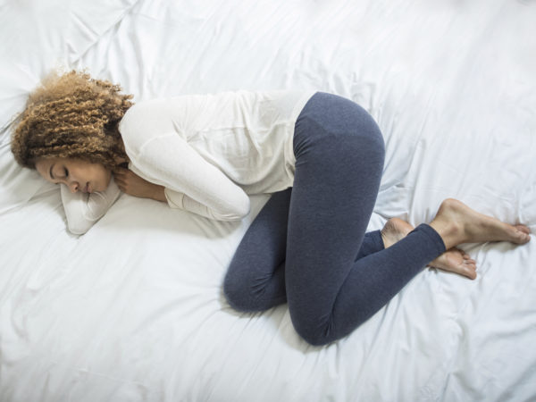 Young African American woman feeling ill and lying down on the bed
