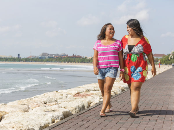 Full figured Asian women walking along the Kuta beachfront in Bali, Indonesia