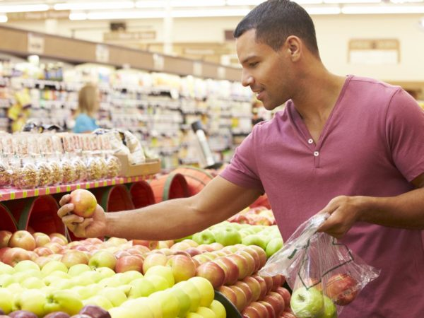Man At Fruit Counter In Supermarket Putting Fruit Into A Bag