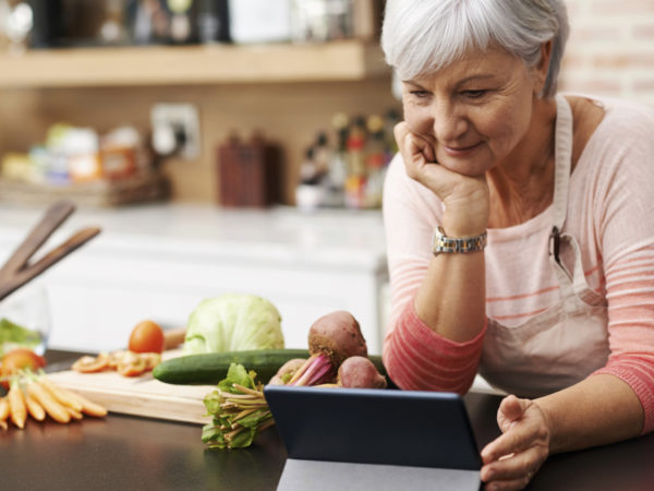 Shot of a woman resting her chin on her hands as she watches a tablet in her kitchen
