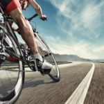 An athlete is riding a bicycle on road. The man is wearing black bike shorts and shin guards along with a red sleeveless top and a red and white helmet and sunglasses. The image is blurred in motion.