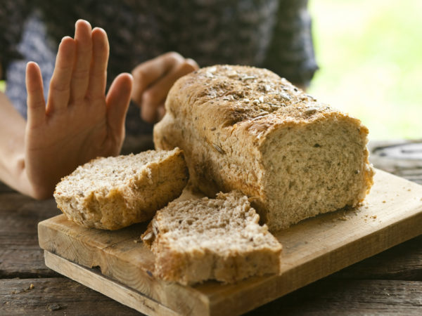 A woman rejecting bread, gluten-free concept. A whole-grain loaf of bread on a rustic wooden table, and a woman rejecting it with a hand gesture.
