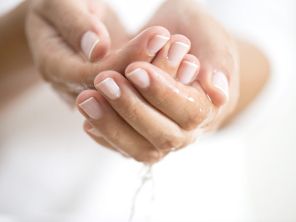 Caucasian female is holding water in hands, horizontal