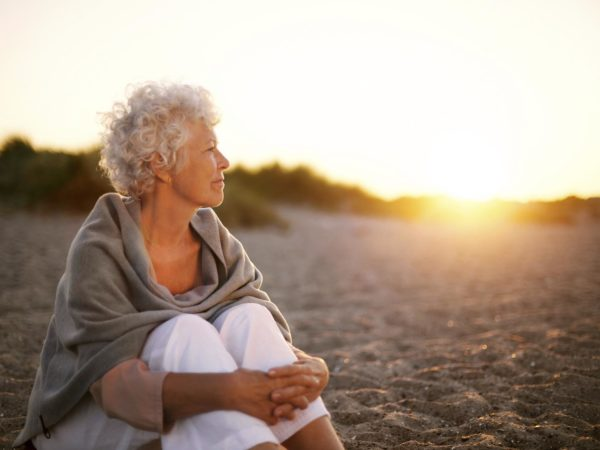 Old woman sitting on the beach looking away at copyspace. Senior female sitting outdoors
