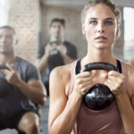 Shot of a group of people doing squats with a kettle bell in a gym