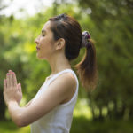Young Asian woman practicing yoga in a garden. healthy lifestyle and relaxation