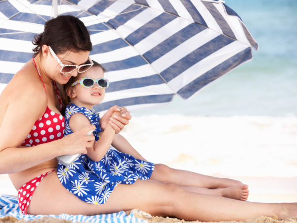 Mother And Daughter Under Beach Umbrella Putting On Sun Cream On Summer Holiday