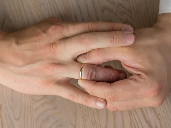 Divorce, separation: hands of married man removing wedding or engagement ring
