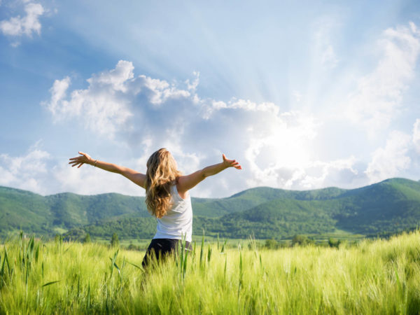 young woman with hands outstretched in the field