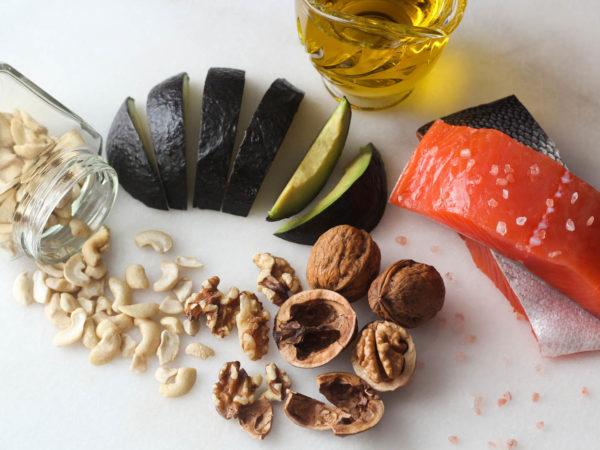 Salmon, olive oil, avocado, walnuts, cashews, rock salt overhead shot on white marble background