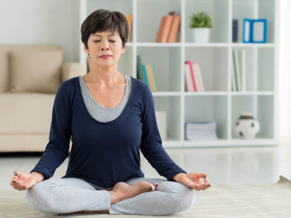 Mature woman sitting on the floor in lotus position