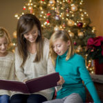 A mother is reading a Christmas story to her two daughters - they are sitting in the living room next to their tree.