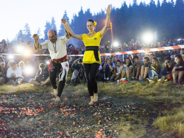 Rozhen, Bulgaria - July 18, 2015: A nestinar man and woman are walking on fire during a nestinarstvo show. The fire ritual involves a barefoot dance on smouldering embers performed by nestinari.