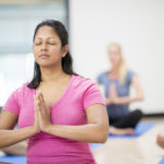 A multi-ethnic group of adults are taking a yoga class together in the gym. They are sitting together and are meditating with their eyes closed on their yoga mats.
