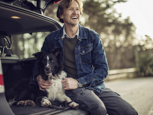 Photo of a man sitting in the car and cuddle his dog