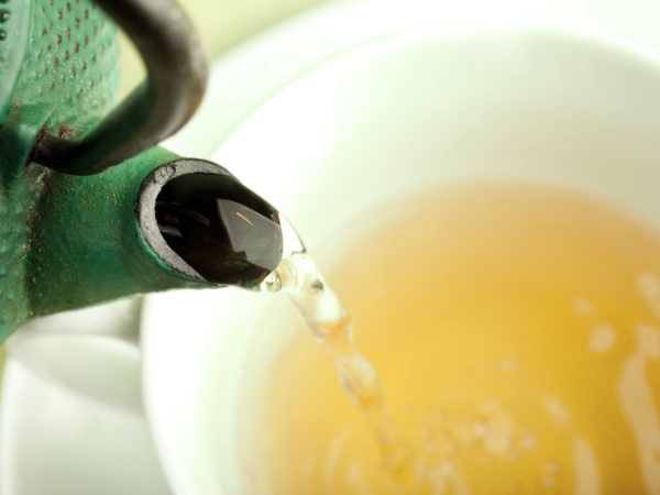 Green tea being poured out of a Japanese teapot, selective focus.