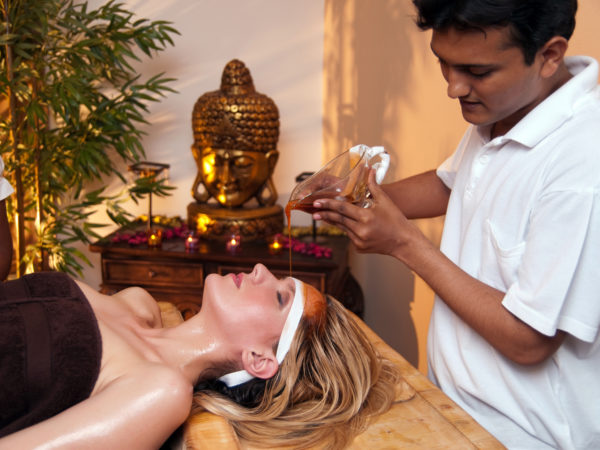 Indian massage therapist doing a Ayurveda massage with aromatic oils.