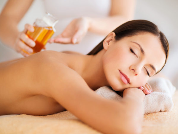 beauty, people, body care and relaxation concept - beautiful woman in spa salon having oil massage