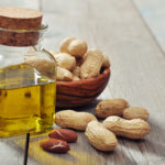 Peanut oil with raw peanuts on wooden background