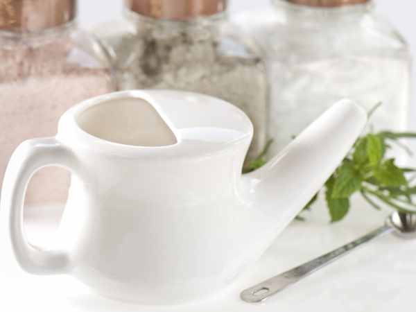 Neti pot for sinus health with salts of different colors and herbs for Ayurvedic technique to administer saline.