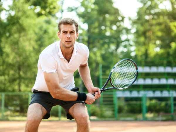 Picture of handsome young man on tennis court. Man playing tennis. Man is ready to hit tennis ball. Beautiful forest area as background