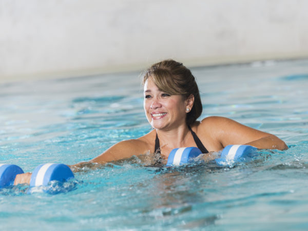 Mature Hispanic woman doing water aerobics with dumbbells in a swimming pool.  She has short brown hair.  She is smiling, happy to get her exercise and stay in shape.
