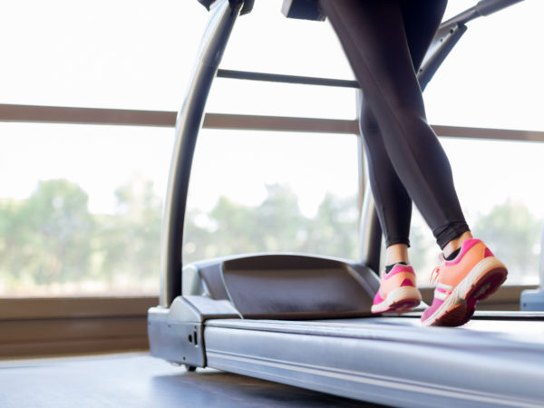 Woman training hard on treadmill, low section, focus on sports shoes