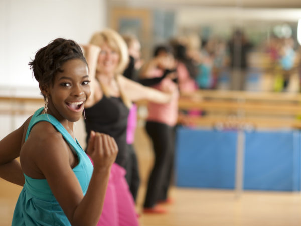 A multi-ethnic group of men and women in a Zumba dance fitness class in an indoor gym studio, standing in a row, wearing exercise clothing, and moving to the music.