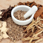 Chinese herb selection with mortar and pestle over mottled background.