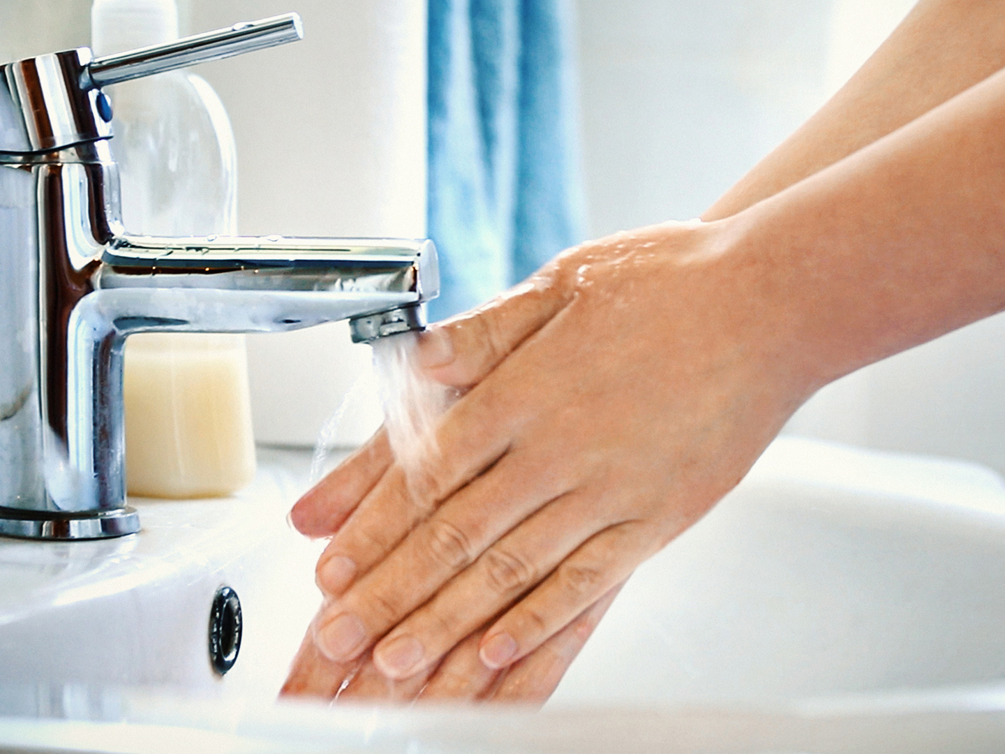 Side view of unrecognizable caucasian woman washing her hands with soap in bathroom. Water is pouring over her hands, visible bluish sink in background.