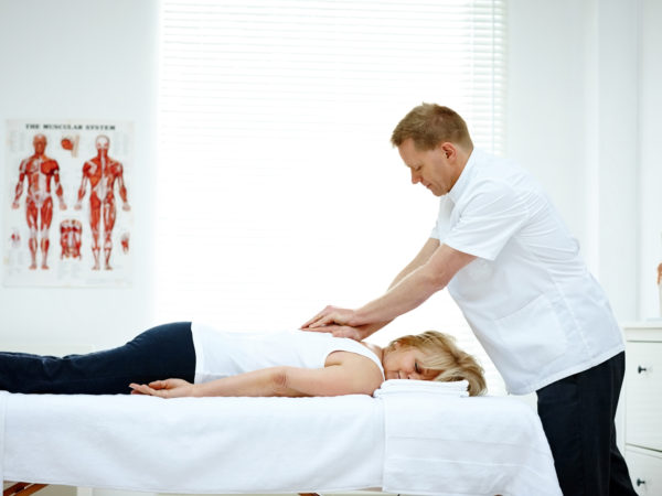 Male osteopath treating back problem of a woman lying on medical room