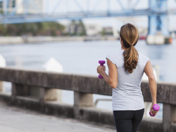 Rear view of mature woman staying fit, running or power walking along the waterfront, carrying dumbbells in her hands.