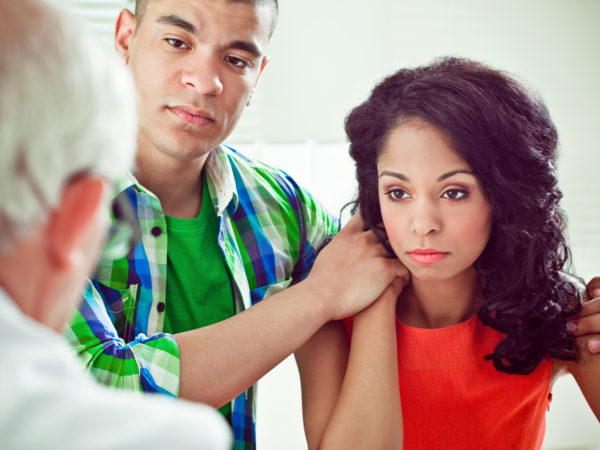 Young adult african american couple getting bad news at doctor visit, worried looking at a doctor and listening to his expertise.