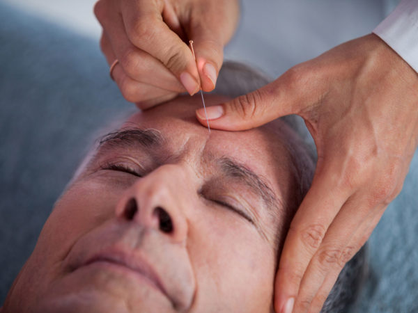 Senior man receiving head massage from physiotherapist in clinic