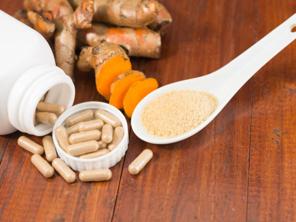 Turmeric herbal capsules in white bottle ,fresh turmeric root and turmeric powder in ceramic spoon on wooden background