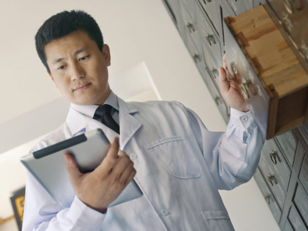 Traditional Chinese doctor looking at tablet computer