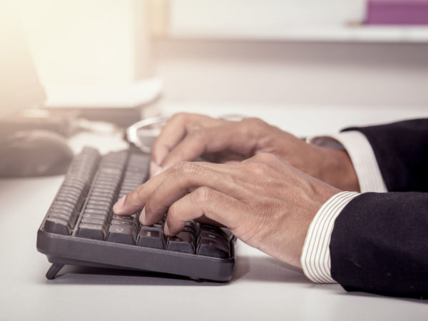 Businessman hand typing on keyboard and working in office in vintage color filter
