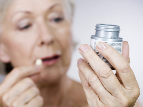 A senior woman holding a bottle of pills