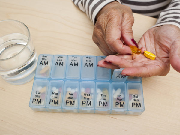 Elderly woman takes her medicine