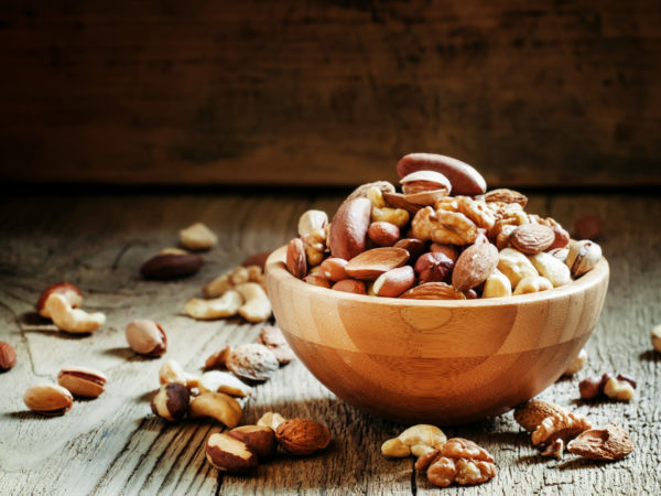 Nuts set in bowl almonds, pistachios, cashews, hazelnuts, peanuts, Brazil nuts, walnuts, vintage wooden background, focus vyboronchy