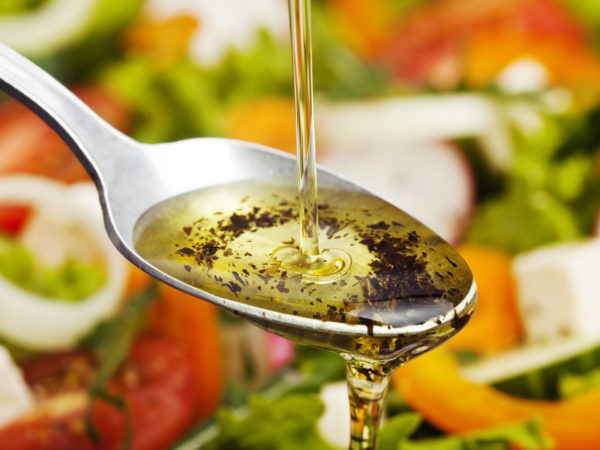 Olive oil pouring over salad.