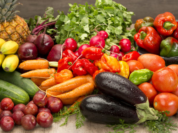 Fresh organic vegetables and fruits on wood table. Horizontal composition.