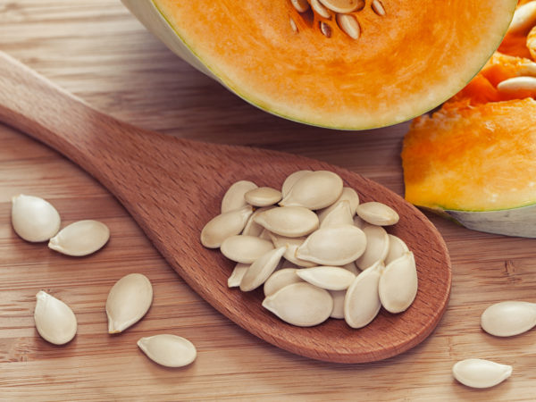 Pumkin seeds inside of wooden spoon near the pumpkin. Close up. Diet concept.