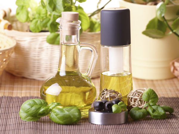 Two bottles with olive oil and grape seed oil with decoration of fresh basil and olives