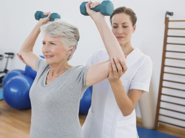 Female trainer assisting senior woman lifting weights in gym